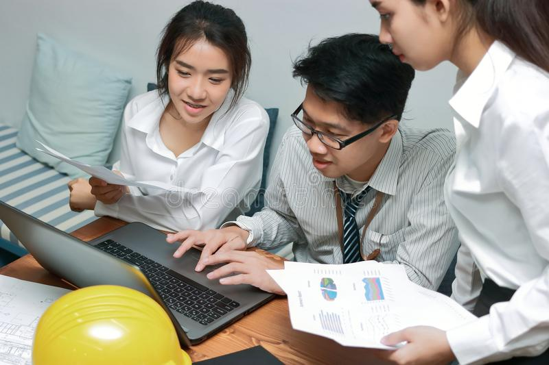 Group of young Asian business people working together on a laptop computer at office. Teamwork brainstroming concept. Selective fo stock image