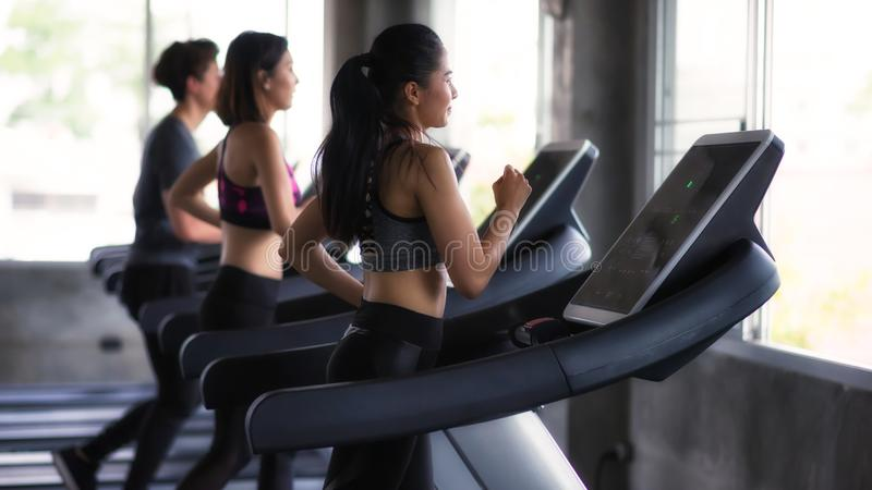Young Asian friends run on treadmills in gym. Group of young Asian female and male friends running on treadmills in sport fitness gym. two women and men run on stock photo