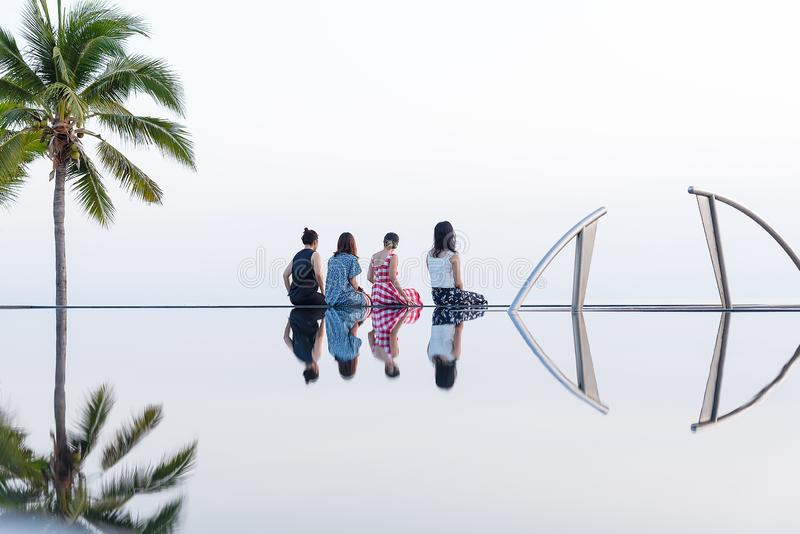 Group of young Asian friend sitting along the swimming pool looking to the sea with beautiful reflection from swimming pool. royalty free stock photo