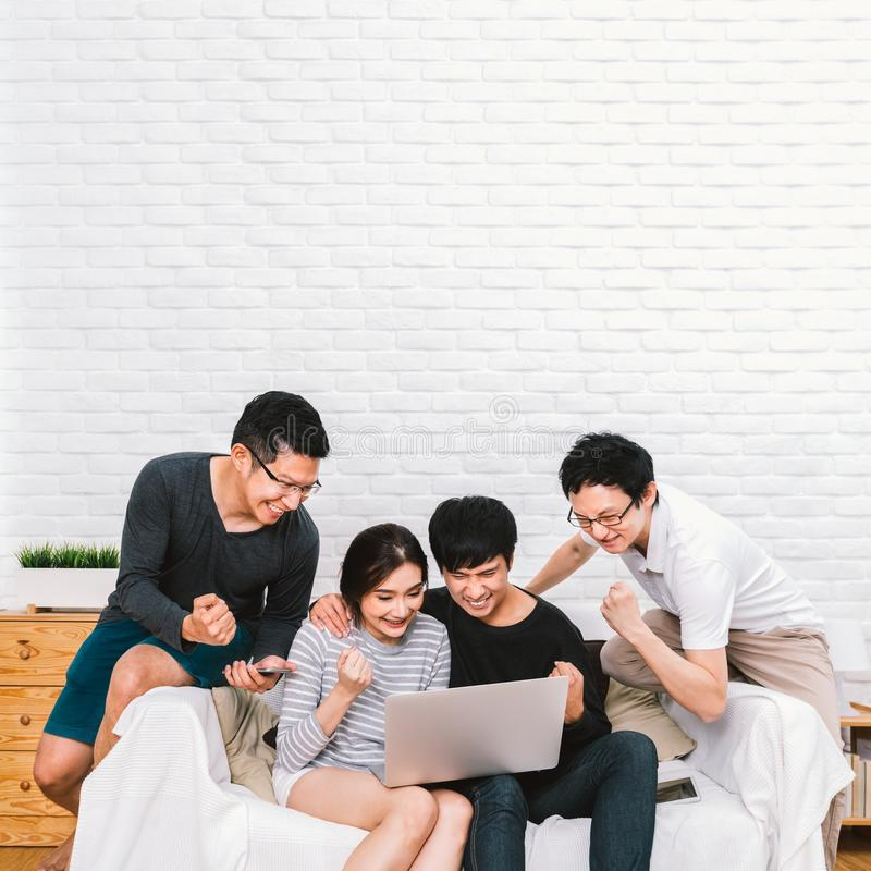 Group of young Asian people cheering together using laptop computer at home with copy space. Success teamwork, friends activity royalty free stock images