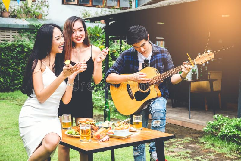 Group of young asian people happy while enjoying garden party and play guitar on garden home royalty free stock photos