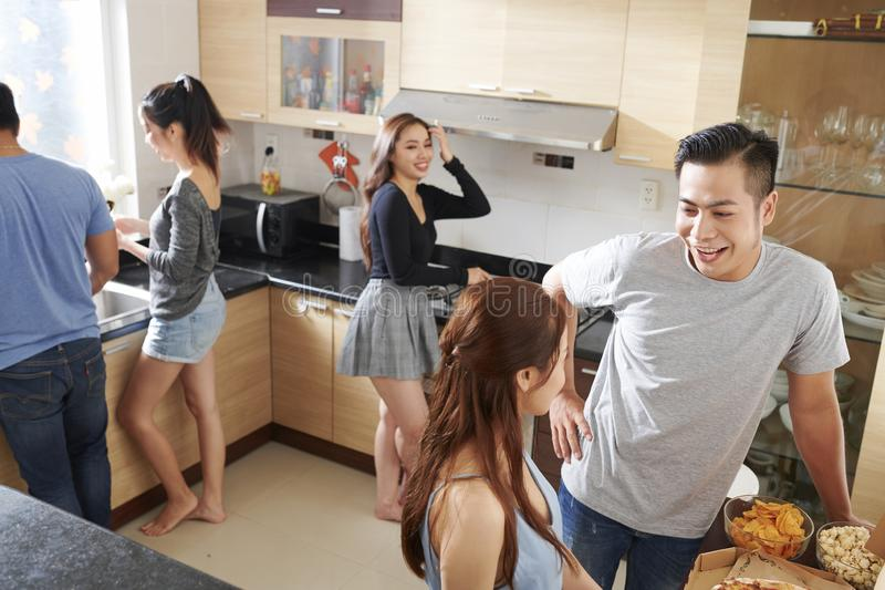 Young people cooking for home party royalty free stock photography