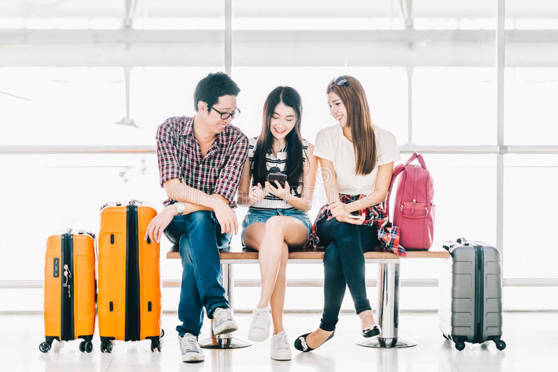 Group of young Asian travelers using smartphone checking flight or online check-in at airport together. With luggage. Travel abroad, summer holiday trip, or stock images