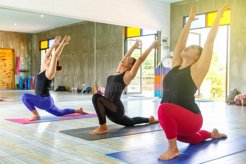 Group of young asians woman practicing during their yoga class in a gym royalty free stock photography