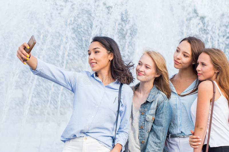 A group of young attractive girls of students makes a selfie on the background of a beautiful fountain royalty free stock images