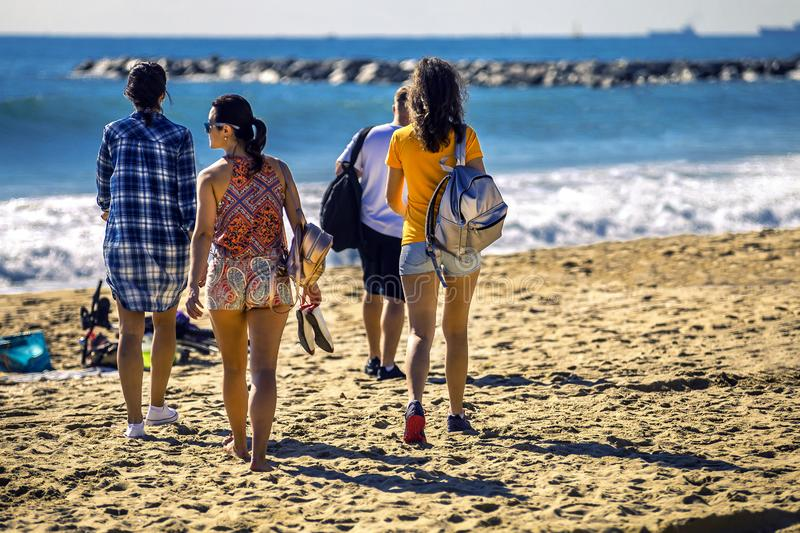 Group of young and attractive people is going along the sandy beach. Group of young and attractive people is going along the sandy beach on sunny day, Barcelona royalty free stock photo
