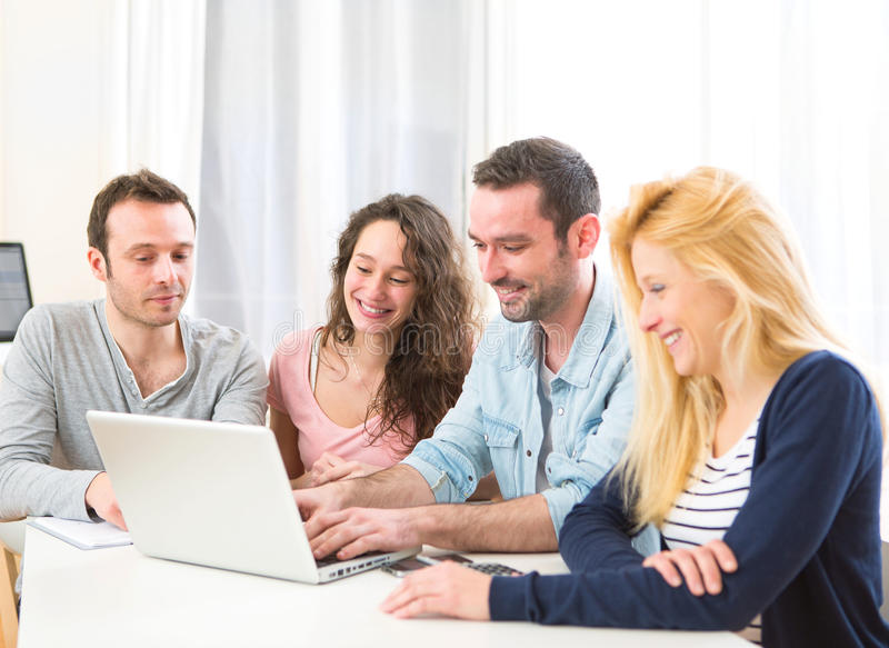 Group of 4 young attractive people working on a laptop. View of a Group of 4 young attractive people working on a laptop stock photos