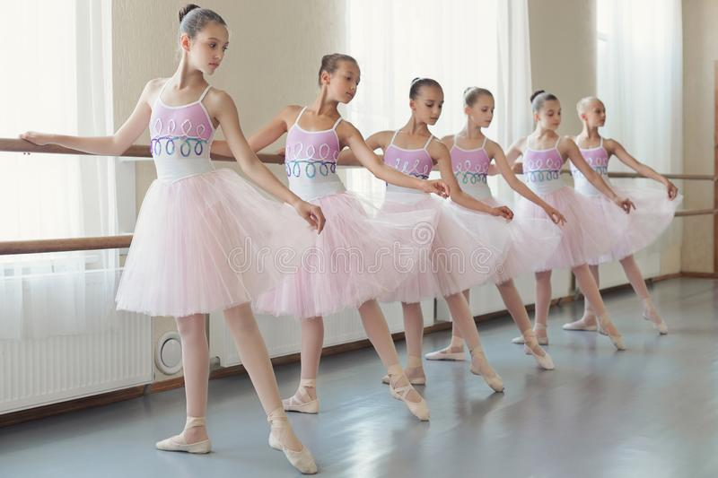 Group of young ballerinas practicing dance at classical ballet school. Preparing for performance. Group of young ballerinas practicing dance at classical ballet stock photo