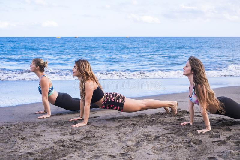 Group of young beautiful caucasian women doing fitness exercises at the beach on the shore. blue ocean and sky in the background. royalty free stock photography