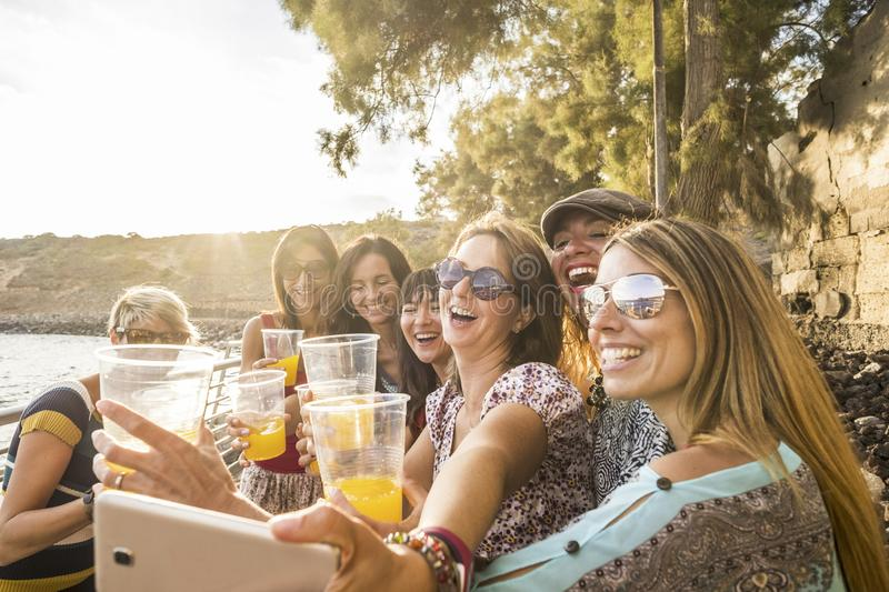 Group of young beautiful caucasian woman taking selfie in vacation leisure activity outdoor near the beach and the ocean. sunset royalty free stock photography