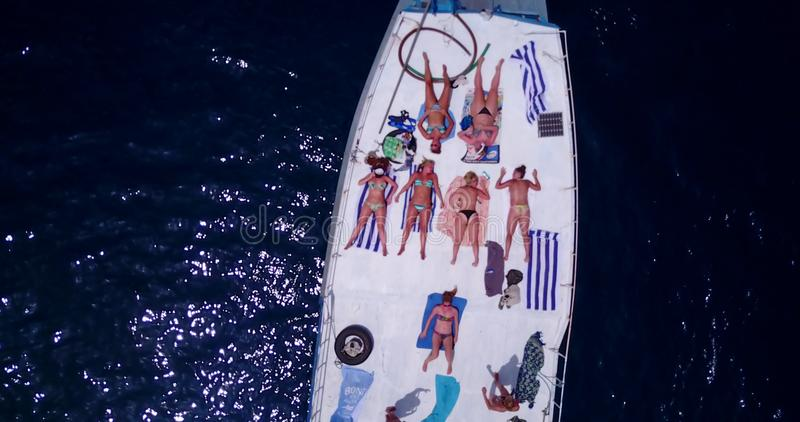 V09150 group young beautiful girls sunbathing on a boat with aerial view in clear aqua blue sea water and blue sky. Group young beautiful girls sunbathing on a royalty free stock photos