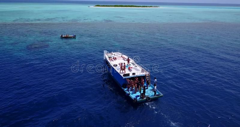 V09131 group young beautiful girls sunbathing on a boat with aerial view in clear aqua blue sea water and blue sky. Group young beautiful girls sunbathing on a royalty free stock photos