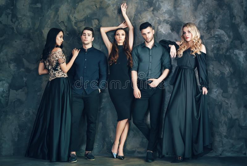 Group of young beautiful people posing in studio. Fashion photo concept royalty free stock images