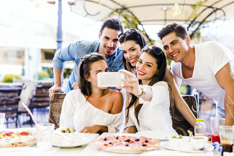Group of young beautiful people sitting in a restaurant and taki. Ng a selfie while smiling stock image