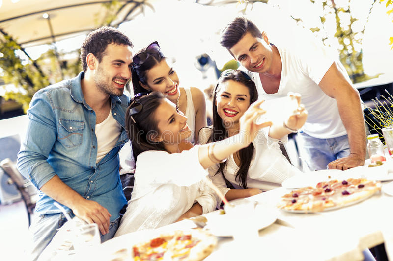 Group of young beautiful people sitting in a restaurant and taking a selfie. While smiling stock photography