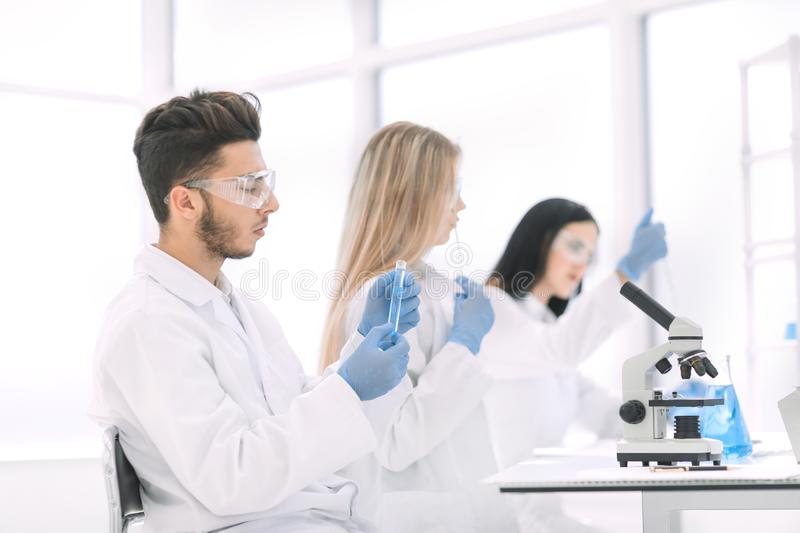 Group of young biologists sitting at the laboratory table stock photos