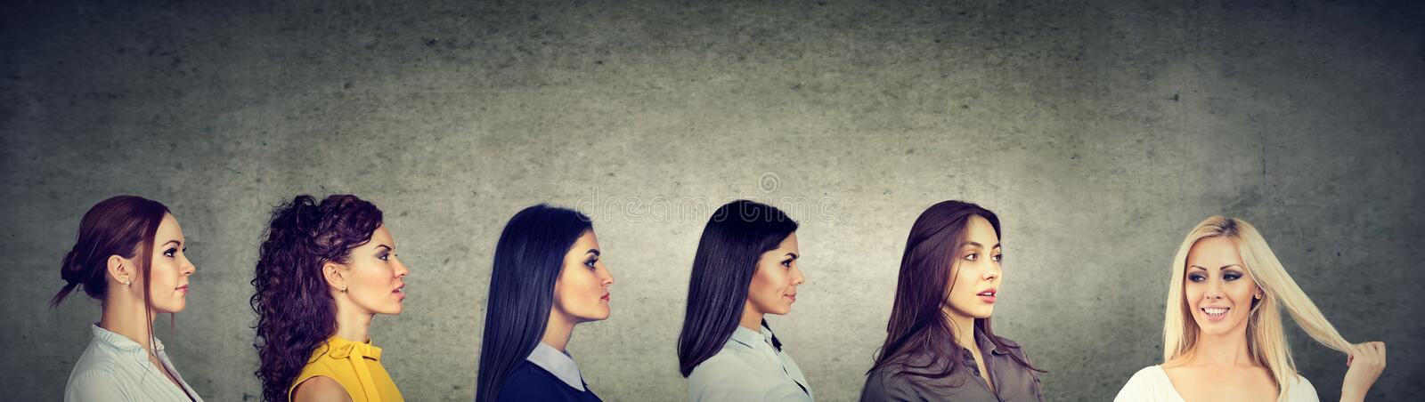 Group of brunette serious women looking at a happy blonde girl royalty free stock image