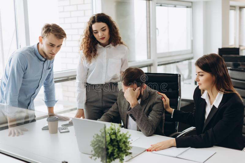 Group of young business partners working in modern office. Coworkers having trouble while working on laptop royalty free stock photo