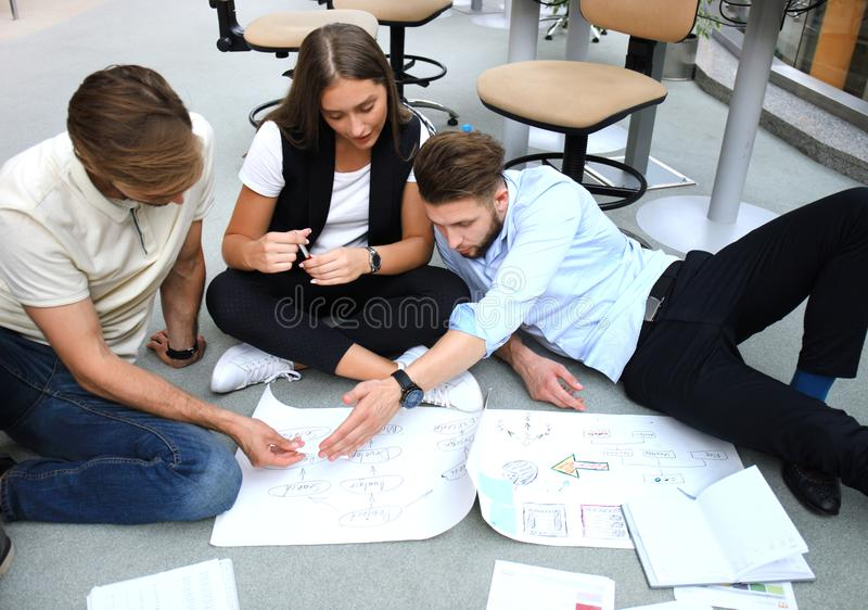 Group of young business people and designers looking at project plan laid out on floor. They working on new project. royalty free stock images