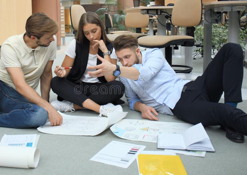 Group of young business people and designers looking at project plan laid out on floor. They working on new project. stock photo