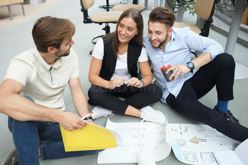 Group of young business people and designers looking at project plan laid out on floor. They working on new project. royalty free stock image