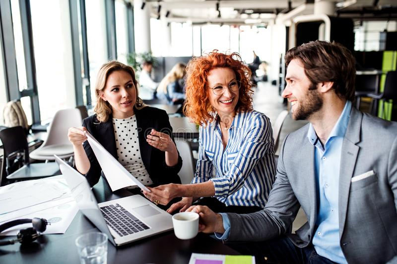 A group of young business people with laptop sitting in an office, talking. royalty free stock photos