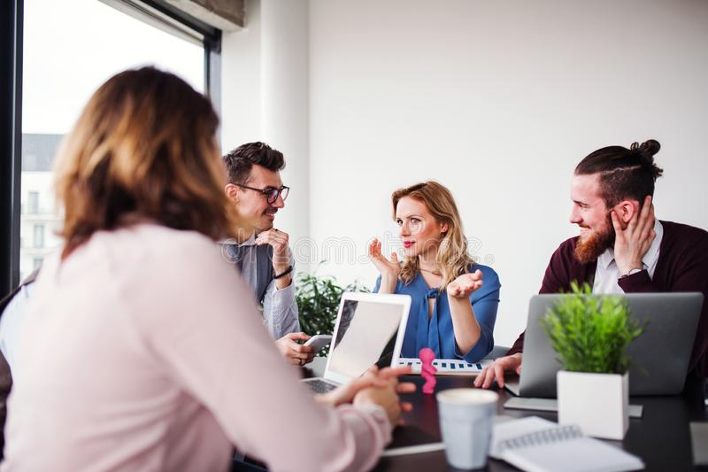 A group of young business people with laptop sitting in an office, talking. royalty free stock image