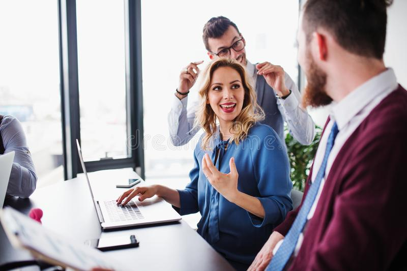 A group of young business people with laptop sitting in an office, talking. stock image