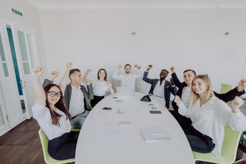Celebrating success. Group of young business people raising their arms and looking happy while sitting around the desk together stock photos