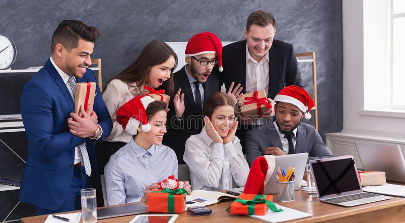 Group of young business people in Santa hats in office stock images