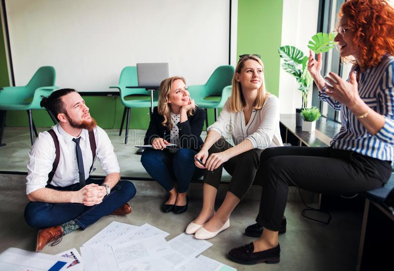A group of young business people sitting on the floor in an office, talking. royalty free stock images