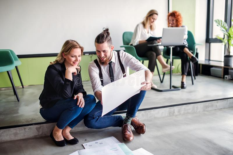 A group of young business people sitting on the floor in an office, talking. stock photos