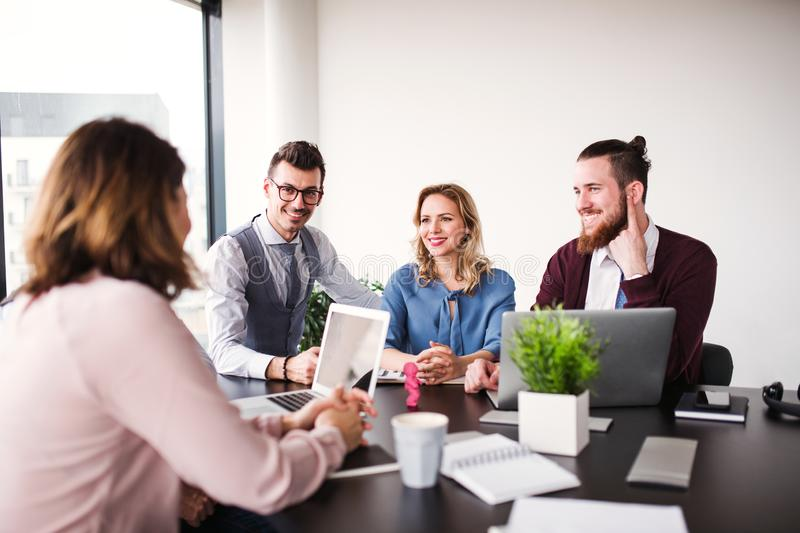 A group of young business people sitting in an office, having meeting. royalty free stock photo