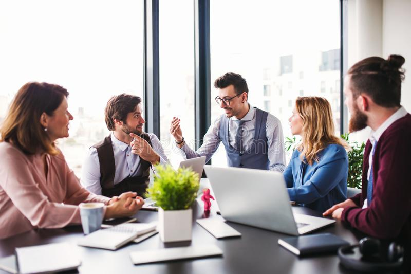 A group of young business people sitting in an office, having meeting. stock photography