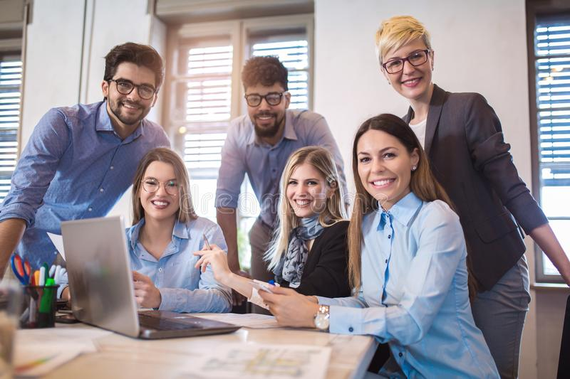 Group of young business people in smart casual wear working together. In creative office using laptop royalty free stock photography