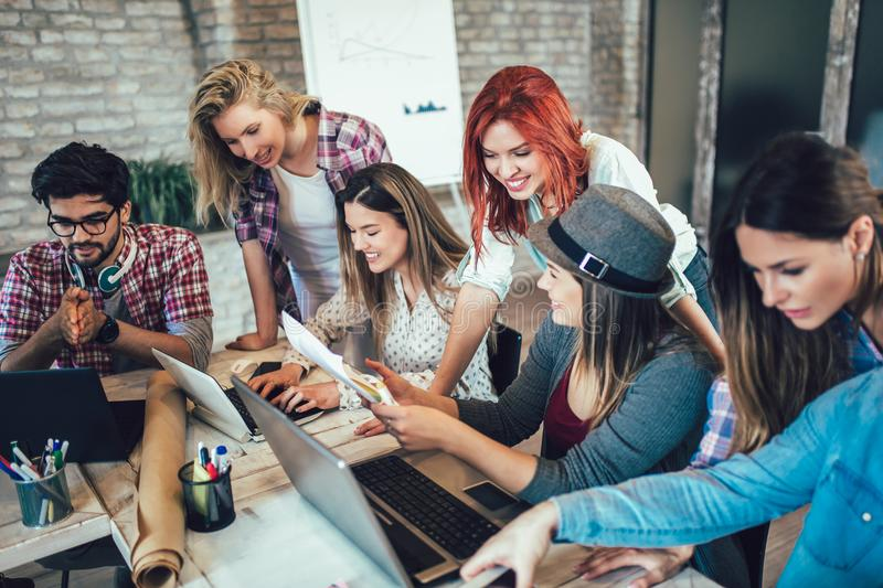 Group of young business people in smart casual wear working together. In creative office stock photography