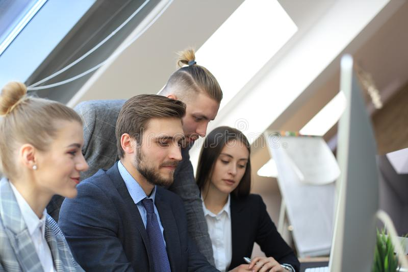 Group of young business people working, communicating while sitting at the office desk together with colleagues.  stock photos