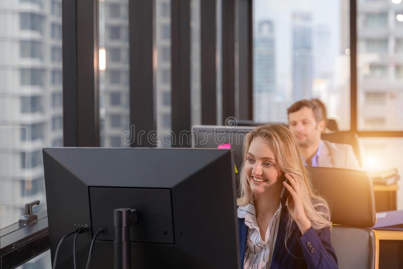 Group of young business people working and communicating while sitting at the office desk together. Business office concept royalty free stock photo