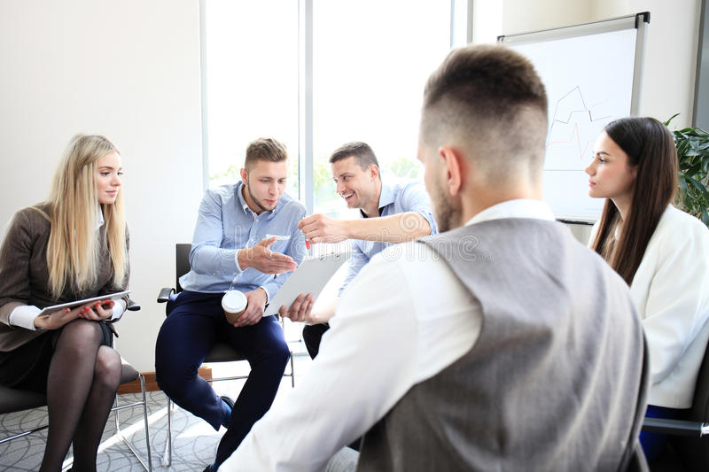 Group of young business professionals. Having a meeting. Diverse group of young designers smiling during a meeting at the office stock image