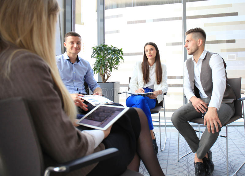 Group of young business professionals. Having a meeting. Diverse group of young designers smiling during a meeting at the office stock photos