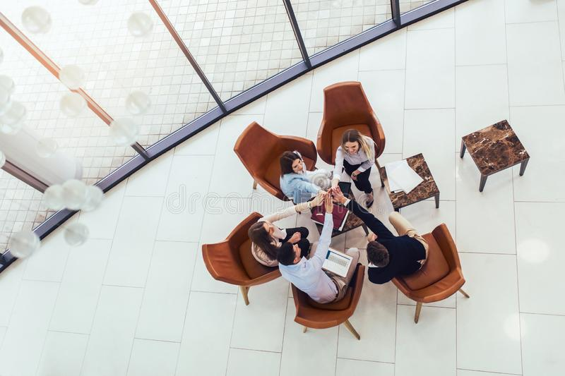 Group of young business professionals sitting together and having casual discussing in office hallway. Top view stock image
