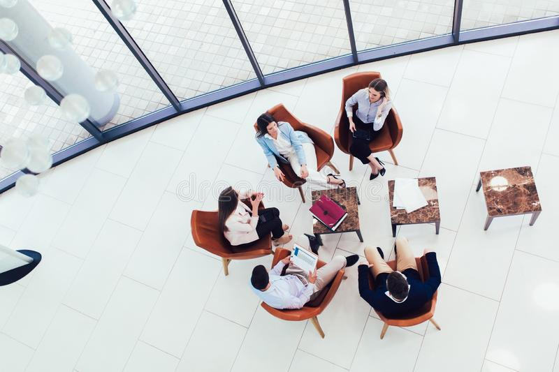 Group of young business professionals sitting together and having casual discussing in office hallway achieving goals. Top view stock image