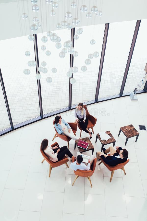 Group of young business professionals sitting together and having casual discussing in office hallway achieving goals. Top view royalty free stock image