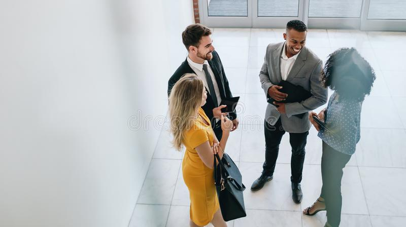 Corporate professionals having casual meeting in office lobby royalty free stock images