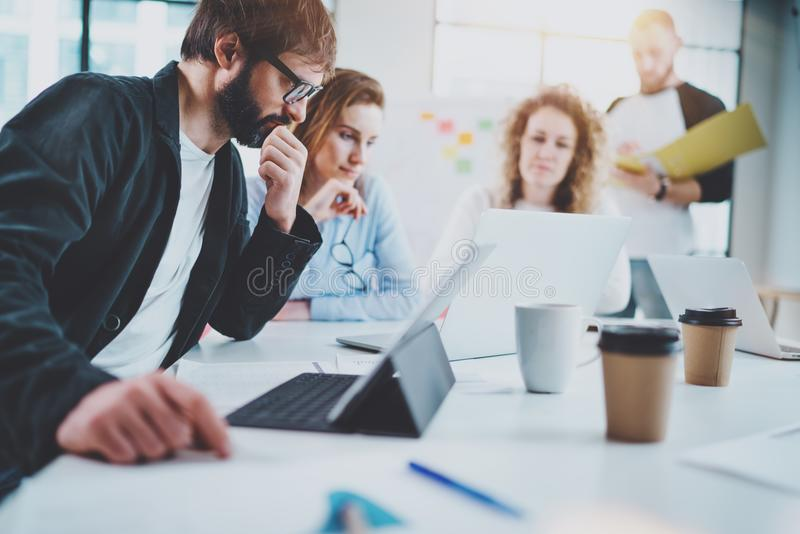 Group of young business team making conversation at sunny meeting room. Horizontal. Blurred background. royalty free stock photography
