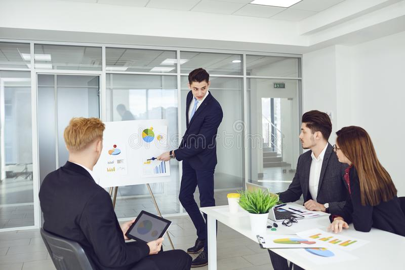 A group of young businessmen are listening to a coach`s speech at office. A group of young businessmen are listening to a coach`s speech. Group of young royalty free stock photography