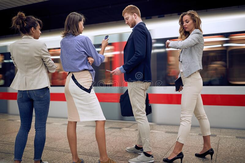 Group of young businesspeople watching at their cell phones, wrist watch, in a subway. time concept stock image