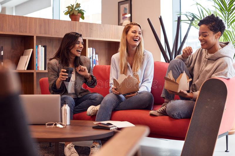 Group Of Young Businesswomen Sitting On Sofas In Open Plan Workspace Having Working Lunch Meeting stock images