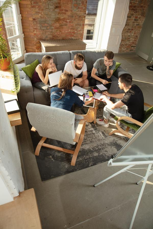 Group of young caucasian office workers have creative meeting to discuss new ideas stock photography