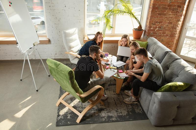 Group of young caucasian office workers have creative meeting to discuss new ideas royalty free stock photo